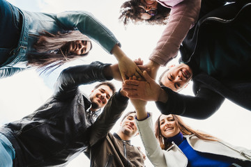 Group of teenagers of different cultures at the park - Teamwork of young people forming a circle - Six men and women having fun together - Bottom view of people putting their hands together