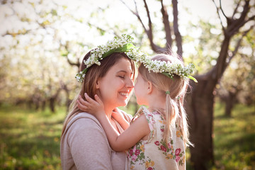 Foto op Textielframe Lelietje van dalen Happy mother and her little daughter in the spring day in a blossoming garden