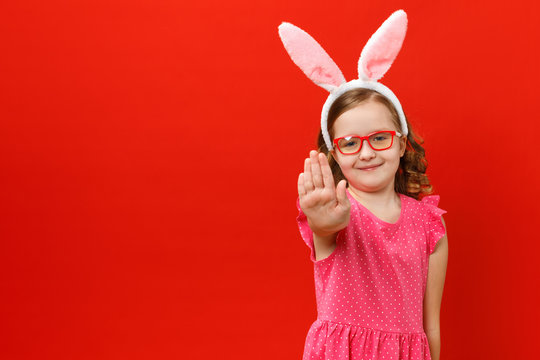 Little girl in easter bunny ears and glasses on a red background. The child shows a stop sign