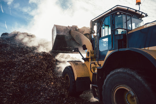 Earth mover working on pile of compost