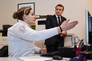 French President Emmanuel Macron listens to a police officer during a visit to the police station in the district of Bourtzwiller, in Mulhouse