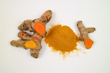 Turmeric powder and turmeric root extracts on a white background are used as a tonic for the body and food ingredients.