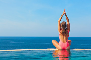 Happy girl relaxing on beach holiday. Young woman in yoga pose meditating at edge of infinity swimming pool with sea view from cliff top. Healthy family lifestyle, summer travel on tropical islands.