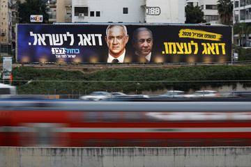Traffic moves past a Blue and White party election campaign poster, depicting party leader Benny Gantz, and Israeli Prime Minister Benjamin Netanyahu, in Tel Aviv