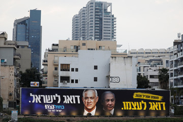 A Blue and White party election campaign poster, depicting party leader Benny Gantz, and Israeli Prime Minister Benjamin Netanyahu, is seen in Tel Aviv