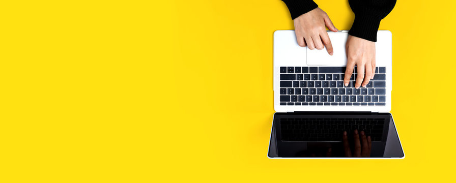 Person using a laptop computer on a solid color background