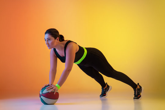 Young caucasian plus size female model's training on gradient orange background in neon light. Doing workout exercises with ball. Concept of sport, healthy lifestyle, body positive, equality.
