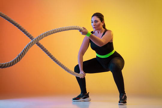 Young caucasian plus size female model's training on gradient orange background in neon light. Training upper body with the fit ropes. Concept of sport, healthy lifestyle, body positive, equality.