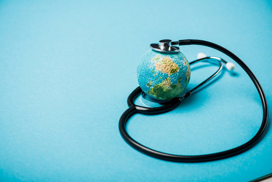 Stethoscope with globe on blue background, world health day concept