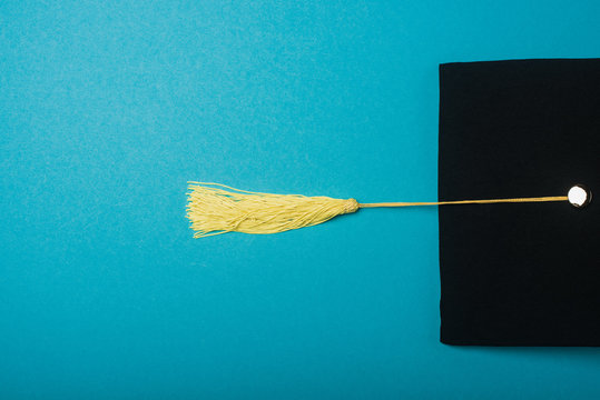 Top view of black graduation cap with yellow tassel on blue background