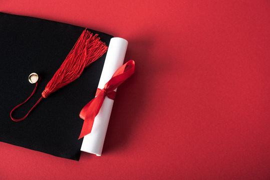 Top view of diploma with beautiful bow and graduation cap with tassel on red background