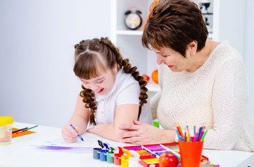 A girl with down syndrome draws at home next to the teacher.