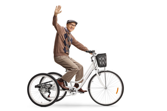 Happy elderly man riding a tricycle and waving at camera