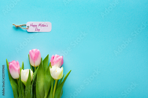 Top view of paper label with happy mothers day lettering and tulips on blue surface with copy space
