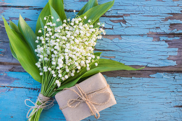 Photo sur Aluminium Muguet de mai Bouquet of lilies of the valley and handmade gift box on blue old paint wooden background. Space for text, flat lay