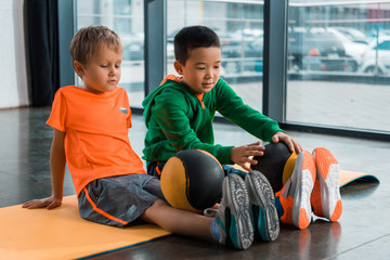 Multicultural children looking on balls on legs and sitting on fitness mat in gym Wall mural