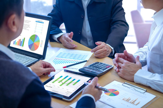 Businessmen tab on tablet touch screen to deeply reviewing a diagram or chart and financial reports for a return on investment or investment risk analysis or business performance.