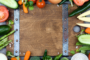 Fresh vegetables and ingredients for cooking around vintage cutting board on rustic background