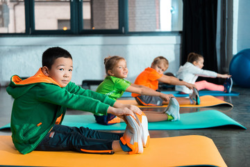 Selective focus of multiethnic kids stretching on fitness mats in sports center Wall mural