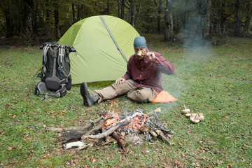 Man Sitting And Drinking On Grass Near Tent, Backpack And Campfire