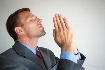 Religious businessman folding his hands in prayer facing his head skyward Fotobehang