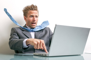 Stressed businessman desperately trying to press the delete button on his laptop computer