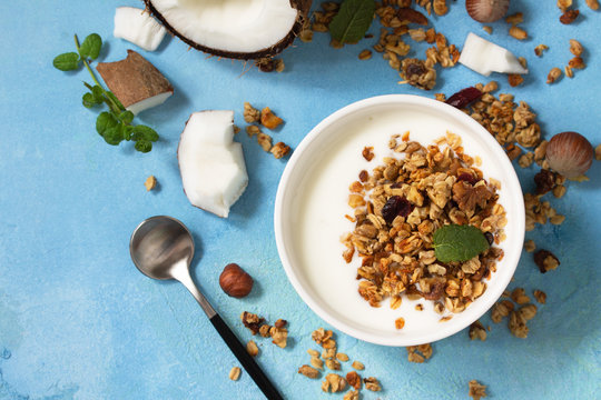 Homemade healthy breakfast. Bowl with homemade baked coconut granola and greek yogurt on a turquoise stone or concrete table.  Top view flat lay background.