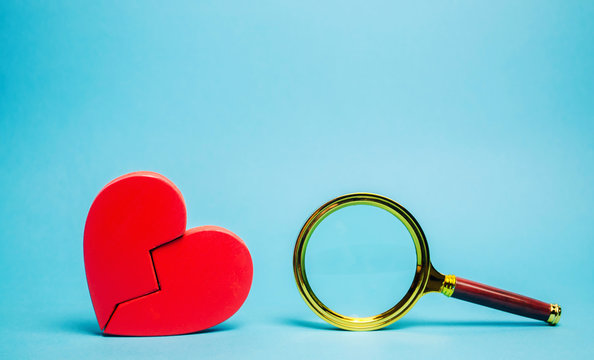 Red heart and a magnifying glass. The concept of finding love and relationships. Find a soul mate. Loneliness. Family psychologist services. Valentine's Day.