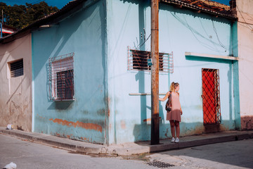 Woman on vacation in light dress and backpack walking on empty cobblestone road among old colorful buildings in Cuba Fotomurales