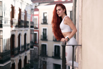 Bright young redhead woman in casual clothes standing at balcony looking at camera