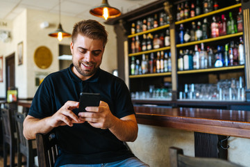 Positive young man in casual wear surfing social media using phone sitting in own bar