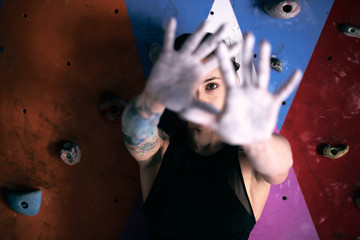 Concentrated strong climber preparing for climbing and showing and looking at camera palms covered with sports talcum powder on background of colorful wall for mountaineering