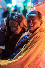 Side view of African American man looking at camera while sitting near girlfriend during date at night on funfair