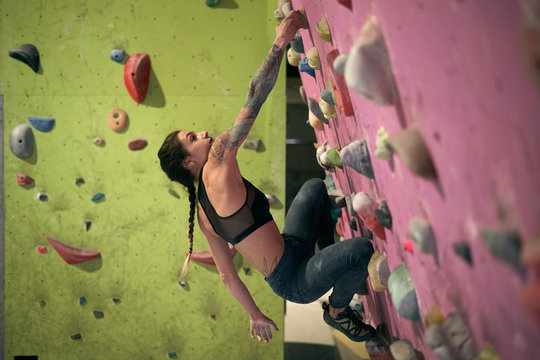 From below side view of woman athlete tattooed powerful woman climbing on colorful wall with ledges for climbers in room