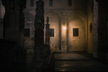 Stone fence with crosses located in dimly illuminated courtyard of aged cathedral at dark night in Burgos, Spain
