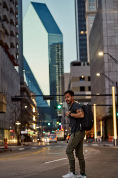 Side view of pleased Hispanic male traveler with backpack in casual outfit laughing while strolling at modern downtown