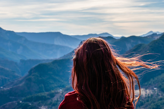 A close-up back view of a young redhead woman with her long hair fluttering in front of the mountain valley landscape from behind on a sunny windy day
