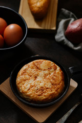 Spanish potato omelette with some fresh eggs shot from high angle over a wooden surface in a dark still life picture. Vertical image.