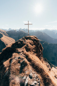 Summit with cross in German Alps against blue sky
