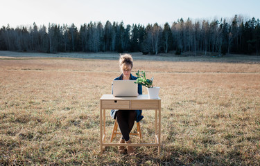 woman flexible working on a desk and laptop outside in a field