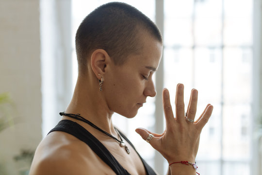 short haired woman practicing yoga meditation near loft window, home i