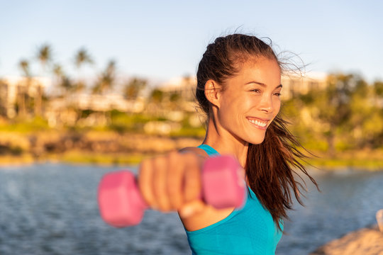 Fitness training Asian girl exercising arms workout with dumbbells doing lateral raises with free weights at outdoor beach summer park. Happy active healthy lifestyle.