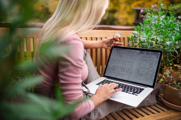 Senior woman architect with laptop sitting outdoors on terrace, working. Fotomurales