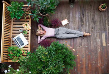 Top view of senior woman with laptop lying outdoors on terrace, resting.