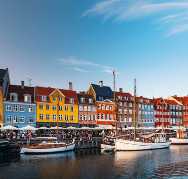 Scenic summer view of canal and Nyhavn pier with colorful buildings, ships, yachts and boats in Old Town of Copenhagen, Denmark. People walking and resting in Copenhagen harbor, scenic summer view
