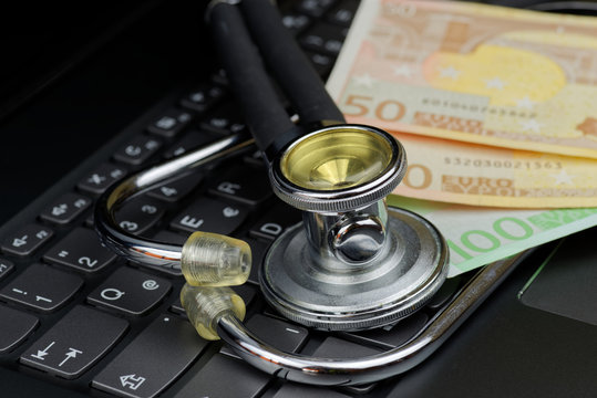 High angle view of stethoscope and euro currency on computer keyboard