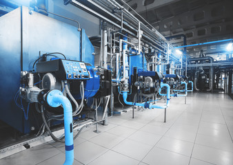 Modern industrial gas boiler room equiped for heating process. Heating gas boilers in a row, pipelines, valves. Blue toning