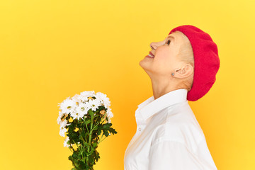 Profile image of stylish mature blonde lady in red bonnet being in good mood smiling broadly with excitement, feeling happy and free, receiving cute bouquet of white dandelion flowers on birthday