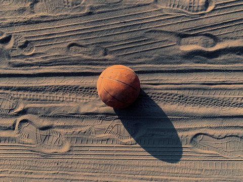The old basketball was thrown onto the Basketball. Footprints in the sand. Traces of car tires in the sand. The end of the match. Old sports equipment.