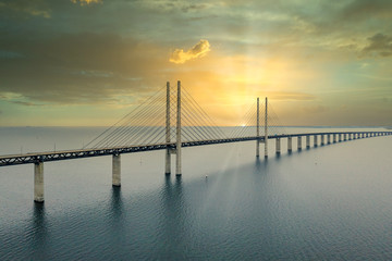 Fototapeten Dunkelgrau The Oresund bridge between Copenhagen Denmark and Malmo Sweden during sunset over the sea.